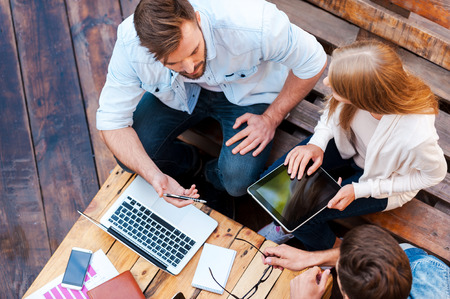 Photo for They can work anywhere! Top view of three young people working together while sitting outdoors - Royalty Free Image