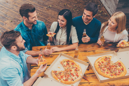 Enjoying time together. Top view of five happy young people holding bottles with beer and eating pizza while standing outdoors