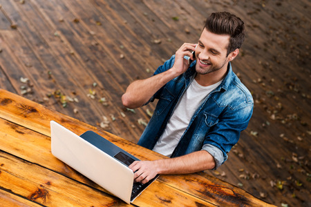 Photo pour Business on fresh air. Top view of happy young man working on laptop and talking on the mobile phonewhile sitting at the wooden table outdoors - image libre de droit