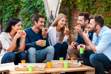 Photo pour Enjoying pizza together. Group of happy young people eating pizza while sitting outdoors - image libre de droit