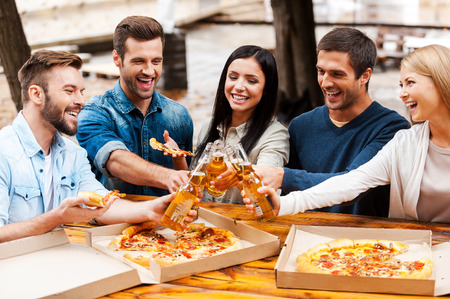 Cheers! Group of cheerful young people eating pizza and cheering with beer while standing outdoors