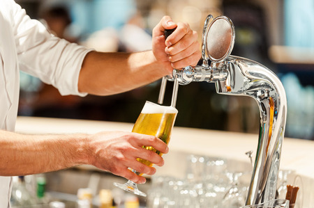 Foto für Pouring fresh beer. Close-up of young bartender pouring beer while standing at the bar counter - Lizenzfreies Bild