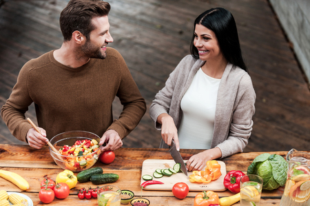 Enjoying cooking together. Top view of beautiful young couple preparing healthy salad together and smiling