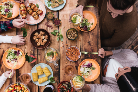 Enjoying great dinner. Top view of four people having dinner together while sitting at the rustic wooden table