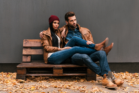 Foto de Enjoying time together. Beautiful young couple bonding to each other while sitting on the wooden pallet with grey wall in the background and fallen leaves on the floor - Imagen libre de derechos