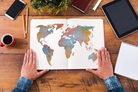Photo pour Planning his journey. Top view close-up image of man holding hands on his notebook with colorful map on it while sitting at the wooden desk - image libre de droit