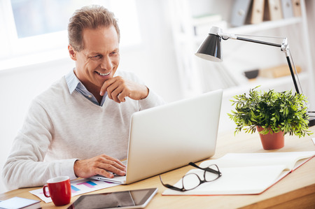 Photo pour Satisfied with his work. Cheerful mature man working on laptop and smiling while sitting at his working place - image libre de droit