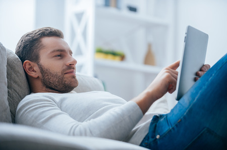 Photo pour Enjoying his leisure time at home. Side view of handsome young man working on digital tablet and looking relaxed while lying on the couch at home - image libre de droit