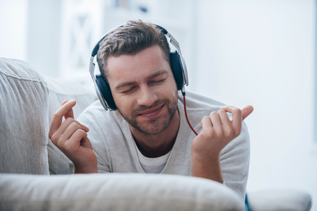 Enjoying his favorite music. Cheerful young man in headphones listening to the music and gesturing while lying on his couch at home