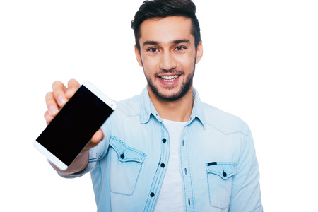Copy space on his smart phone. Confident young Indian man showing his smart phone and smiling while standing against white background