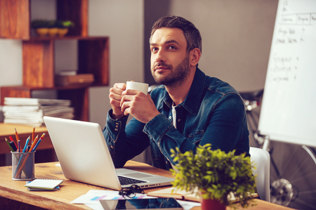 Waiting for inspiration. Thoughtful young man holding coffee cup and looking away while sitting at his working place in office