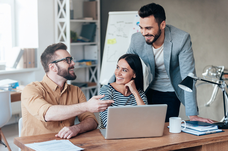 Foto de Finding solution together. Group of confident business people in smart casual wear discussing something while sitting at the desk in office - Imagen libre de derechos