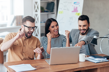 Photo for Celebrating success. Three happy business people in smart casual wear looking at the laptop and gesturing - Royalty Free Image