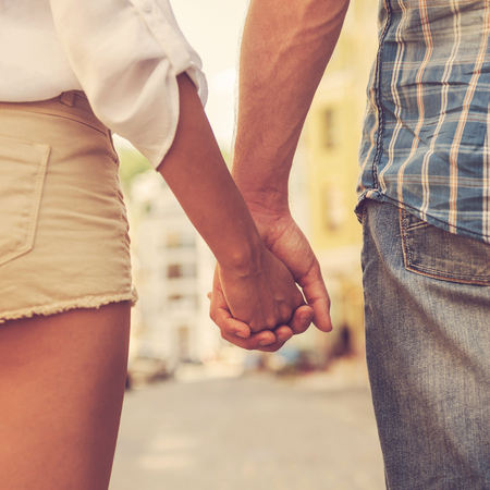 Foto de Hands and hearts together. Close-up of loving couple holding hands while walking outdoors - Imagen libre de derechos
