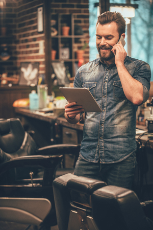 Photo pour our appointment is on Monday! Cheerful young bearded man talking on mobile phone and looking at digital tablet while standing at barbershop - image libre de droit