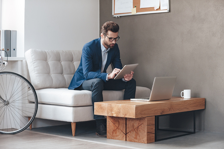 Foto de Multitasking. Handsome young man wearing glasses and working with touchpad while sitting on the couch in office - Imagen libre de derechos