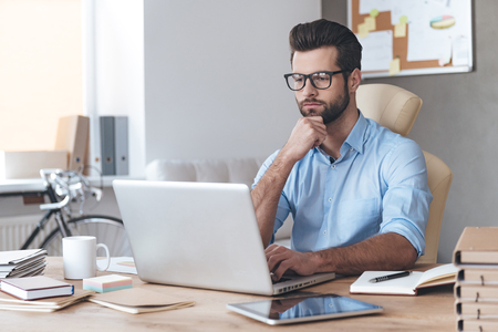 Photo for Busy working. Pensive young handsome man wearing glasses working on laptop and keeping hand on chin while sitting at his working place - Royalty Free Image