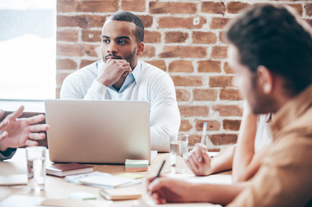 Listening to new business strategy. Thoughtful young African man holding hand on chin and listening while his coworkers discussing something sitting at the office table