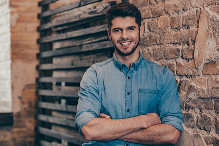 Photo for Smiling and handsome.Handsome young man keeping arms crossed and looking at camera with smile while standing against brick wall - Royalty Free Image