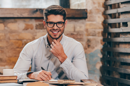 Working with pleasure. Handsome young man in glasses making some notes in his note pad and looking at camera with smile while sitting at his working place