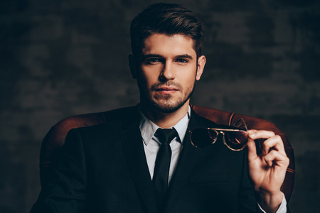 Photo pour Breathtaking look.Portrait of young handsome man in suit holding his sunglasses and looking at camera while sitting in leather chair against dark grey background - image libre de droit