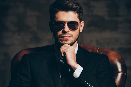 Photo pour Elegant and perfect.Portrait of young handsome man in suit holding hand on chin and looking at camera while sitting in leather chair against dark grey background - image libre de droit
