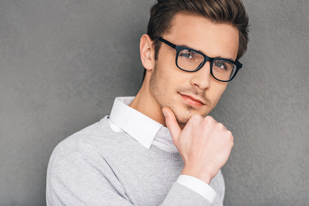 Photo for Confident and intelligent. Confident young man in glasses holding hand on chin and looking at camera while standing against grey background - Royalty Free Image