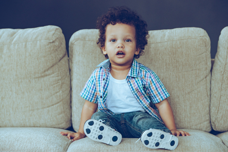 Photo pour One hundred percent cute! Little African baby boy looking at camera while sitting on the couch at home - image libre de droit