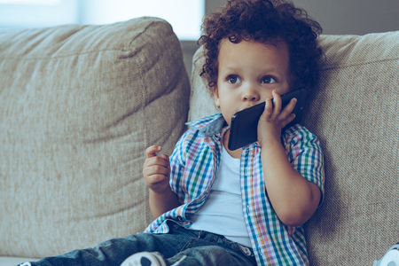 Photo pour Hello Grandma! Little African baby boy talking on mobile phone and looking away while sitting on the couch at home - image libre de droit