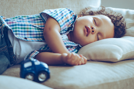 Photo pour Sweet dreams. Little African baby boy sleeping while lying on couch at home - image libre de droit