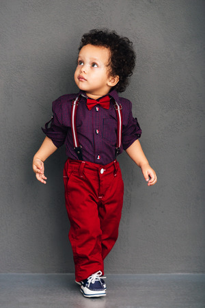 Photo pour Like on catwalk. Little African baby boy looking away while walking against grey background - image libre de droit