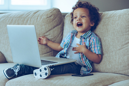 Photo pour Mom how does this thing turns on?Little African baby boy keeping mouth open while sitting on the couch at home with laptop on his knees - image libre de droit