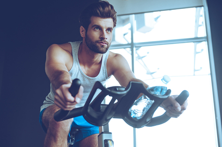 Photo pour Confident cycler. Low angle view of young man in sportswear cycling at gym - image libre de droit