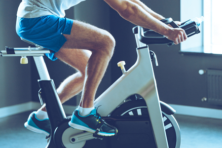 Photo for Best cardio workout. Side view part of young man in sportswear cycling at gym - Royalty Free Image