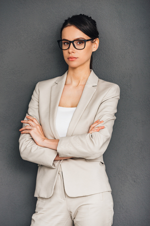 Ms. Confidence. Beautiful young businesswoman in glasses keeping arms crossed and looking at camera while standing against grey background