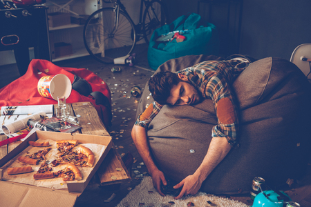 Young handsome man passed out on bean bag with joystick in his hand in messy room after party
