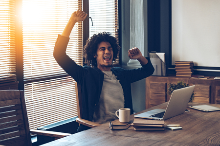 Photo pour Excited young African man gesturing and keeping mouth open while sitting at his working place - image libre de droit