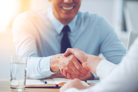 Foto de Good deal. Close-up of two business people shaking hands while sitting at the working place - Imagen libre de derechos
