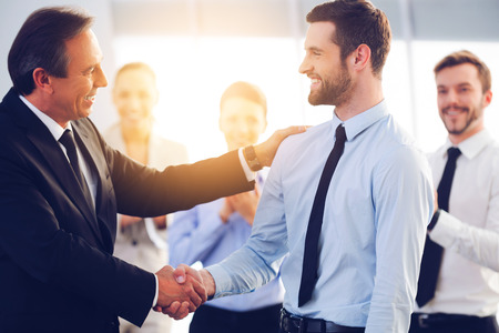 Photo for Great job! Two cheerful business men shaking hands while their colleagues applauding and smiling in the background - Royalty Free Image
