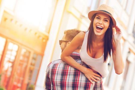 Foto de Enjoying beautiful day. Rear view of young cheerful man carrying his beautiful girlfriend on shoulder while walking by the street - Imagen libre de derechos