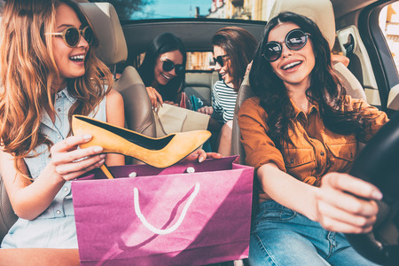 Foto de Next stop is lingerie shop! Four beautiful young cheerful women holding shopping bags and looking at each other with smile while sitting in car - Imagen libre de derechos