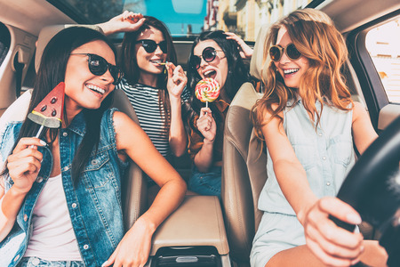 Photo pour Great start of their journey. Four beautiful young cheerful women looking at each other with smile and holding lollipops while sitting in car - image libre de droit