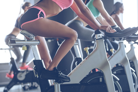 Photo pour Power and motivation. Side view part of young women with perfect bodies in sportswear looking at camera with smile while cycling at gym - image libre de droit