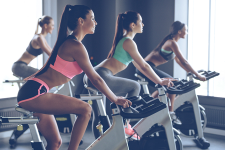 Photo pour Beautiful ride. Side view of young beautiful women with perfect bodies in sportswear looking away with smile while cycling at gym - image libre de droit