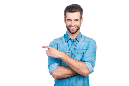 Photo for Happy young handsome man in jeans shirt pointing away and smiling while standing against white background - Royalty Free Image