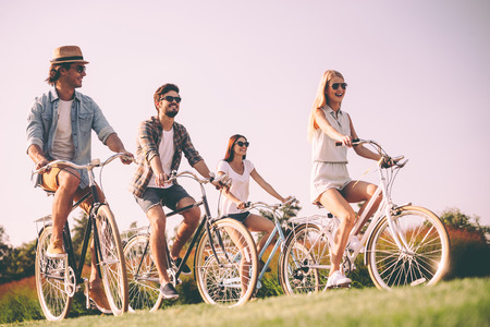Photo pour Cycling with best friends. Group of young people riding bicycles and looking happy - image libre de droit