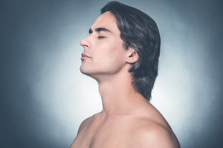 Photo pour Fresh and clean. Side view of young shirtless man keeping eyes closed and looking calm while standing against grey background - image libre de droit