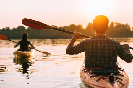 Foto de Meeting sunset on kayaks. Rear view of beautiful young couple kayaking on lake together with sunset in the background - Imagen libre de derechos