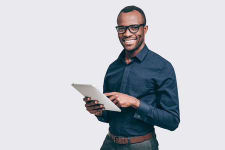 How may I help you? Handsome young African man holding digital tablet and looking at camera with smile while standing against grey background