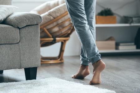 Photo pour Warm floor concept. Close-up of female legs stepping by hardwood floor at home - image libre de droit
